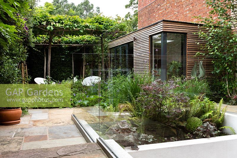 View of paved, modern garden with panelled summerhouse and trained espalier tree arch.