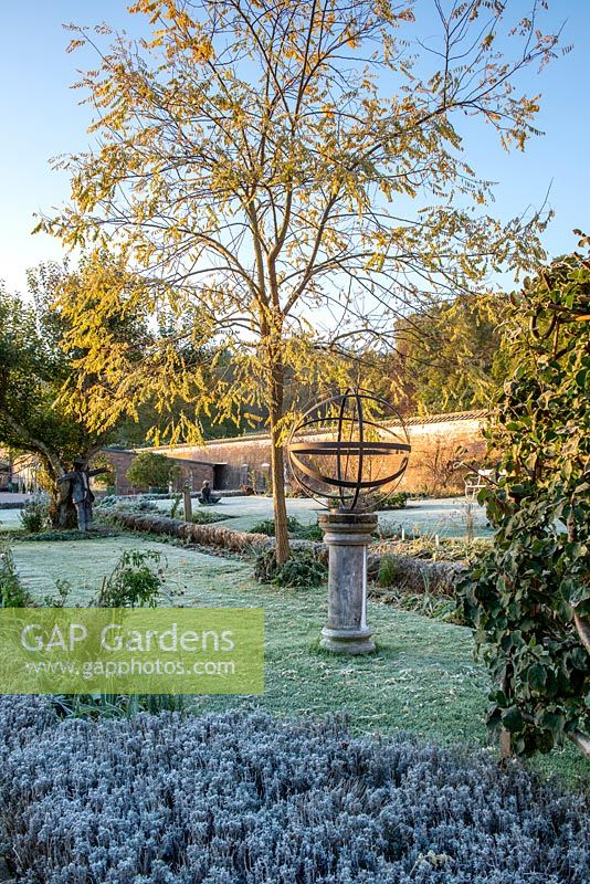 View of metal sundial on a frosty morning in the walled garden.