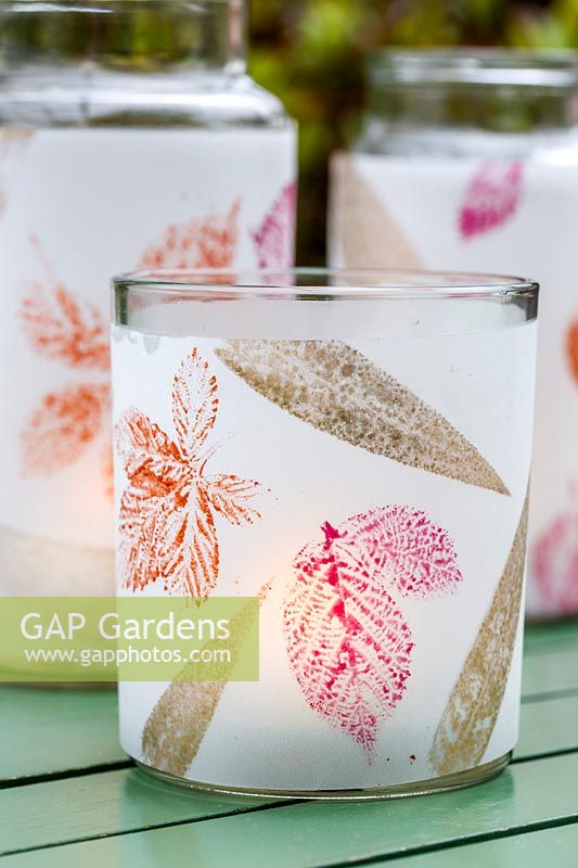 View of alternative candle holders, glass jars decorated with leaf prints.
