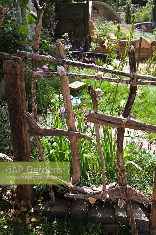 Driftwood fence. 'Postcard From Wales' Garden, RHS Chelsea Flower Show.