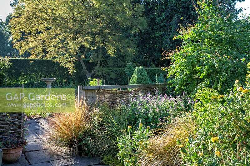 Fence and borders at Stillingfleet Lodge garden, Yorkshire, UK