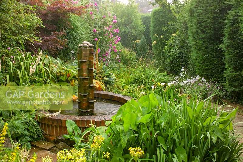 Brick pond and water feature in plantsman's garden. Collepardo, Newton Abbott, Devon, UK.