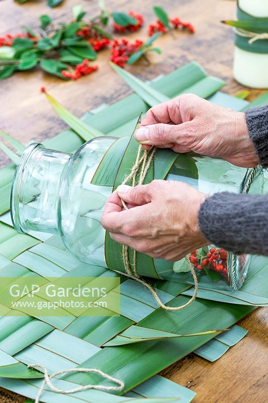 Woman securing Phormium leaf around glass jar with jute string.
