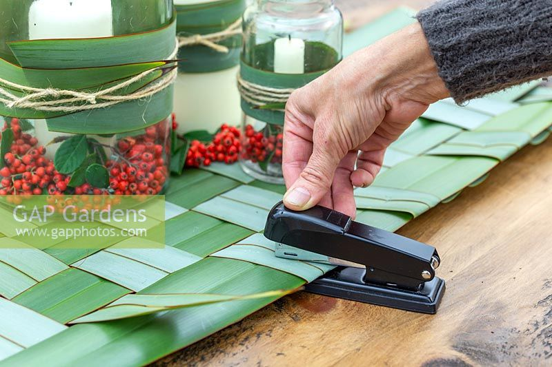 Woman using stapler to secure woven phormium leaves in place.