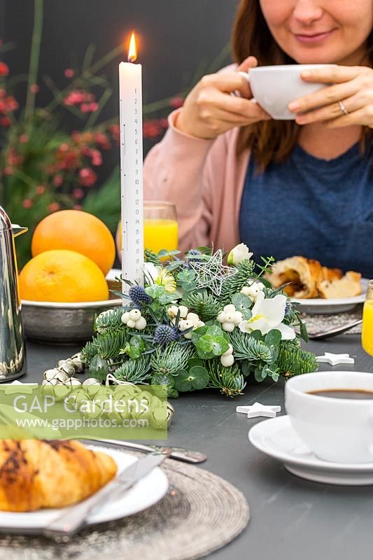 Woman at breakfast table with advent candle arrangement centrepiece.
