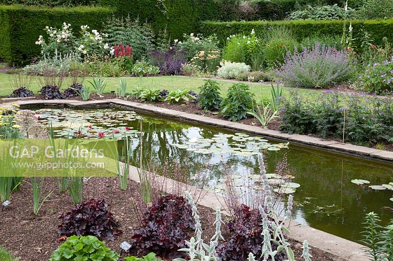 Large formal pond and herbaceous borders in the garden of David Austin Roses.