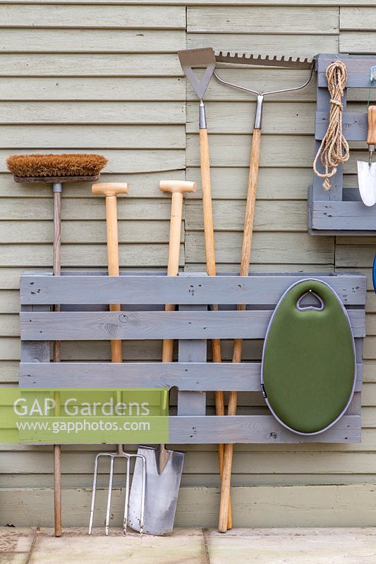 Pallet storage organiser, split painted pallet used for storing tools and gardening equipment.