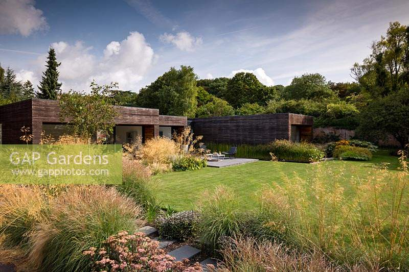 View across perennial and ornamental grass borders towards lawn and contemporary house