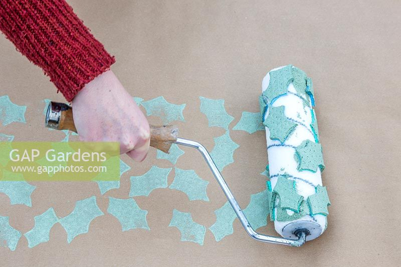 Using roller with foam patterns to create holly pattern on craft wrapping paper.