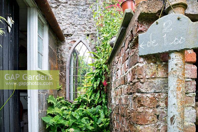 Slate sign with directions to the toilet in small alley with arched mirror and ferns.