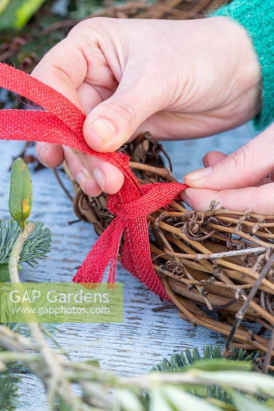 Creating a hanging hoop for wreath out of red hessian ribbon