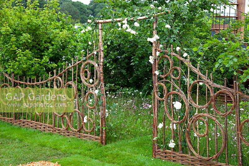 Hazel and willow decorative fence in pattern of circles either side of an arch, in the show garden 'Belmond Enchanted Gardens