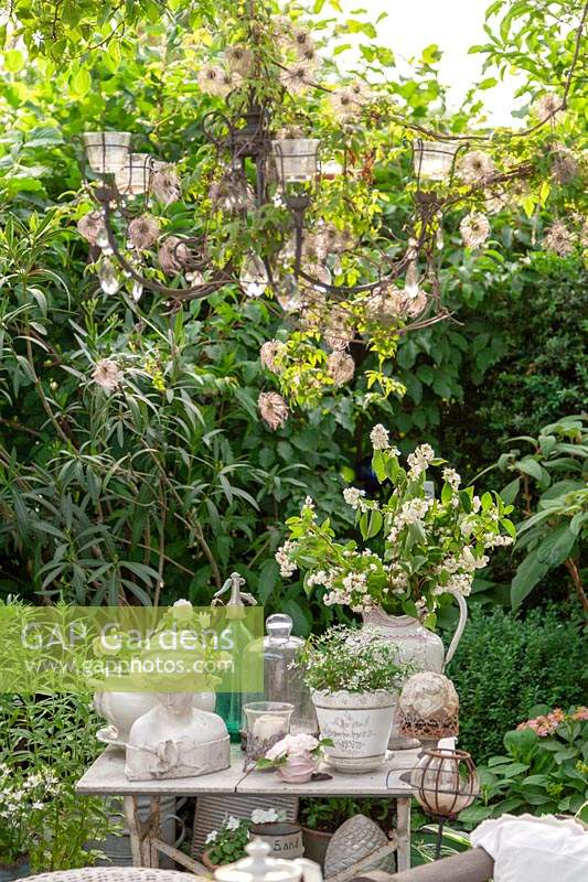 Old decorative objects displayed on vintage table with a hanging chandelier draped with clematis