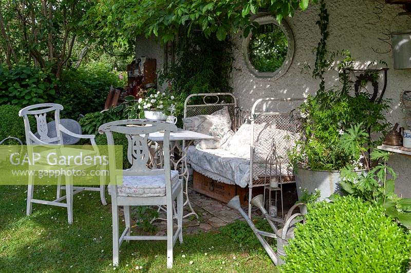 Relaxing area in shade, an old decorative bed, antique chairs and planted pots