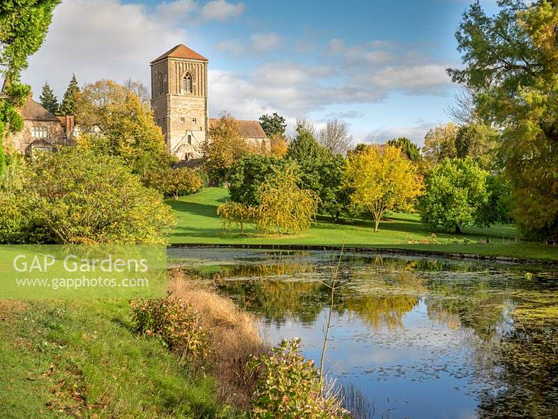Little Malvern Church and the lawn with trees covered with autumn leaves reflected in the lake.