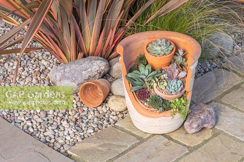 Finished succulent landscape pot created with a broken pot and terracotta crocks.