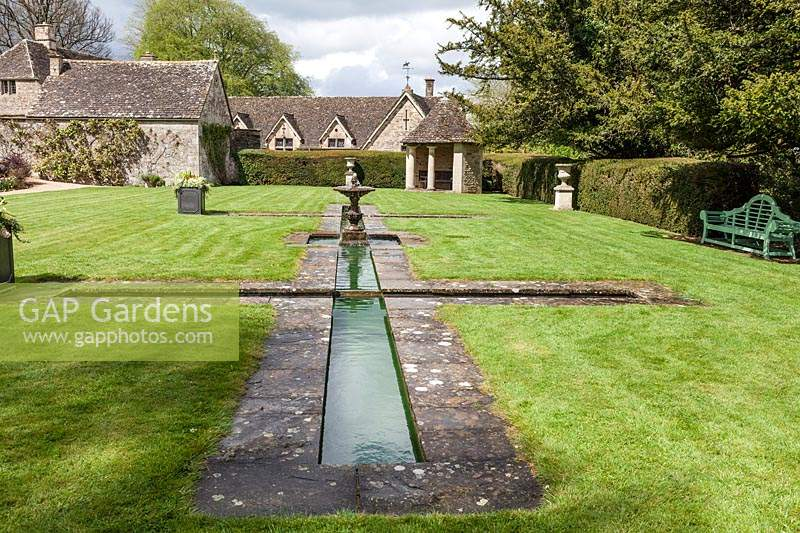 Fountain and formal pool next to the house. Miserden garden, near Stroud, Gloucestershire, UK.