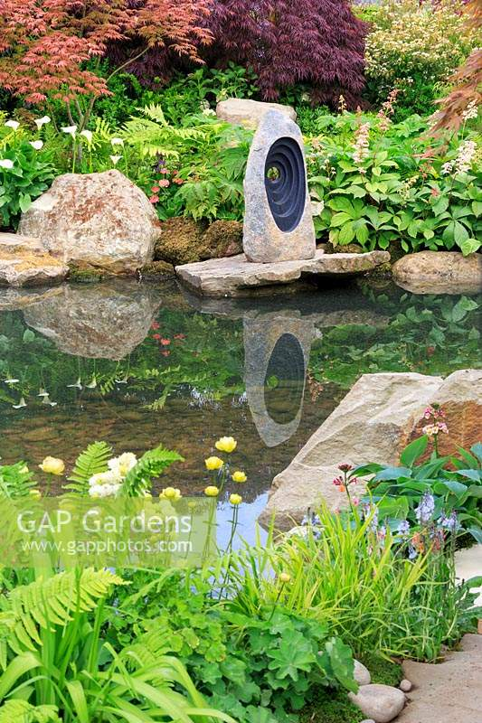 A Meditation Garde view to the focal stone sculpture on rocks reflected in 