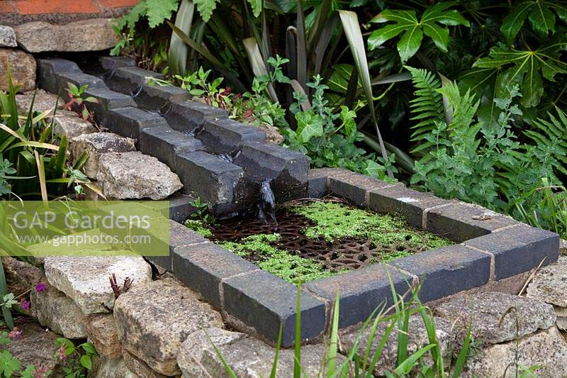 Raised brick rill feeding water into a well with metal grill