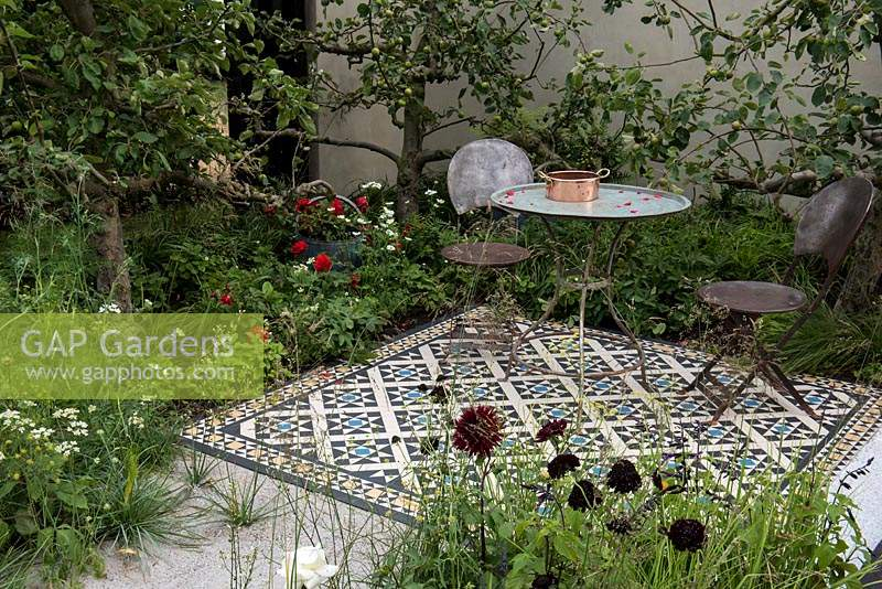 A modern antiquaria garden with a tiled terrace surrounded by apple trees that are under planted with red roses, alpine strawberries, fennel, Orlaya grandiflora and Dahlia. The Style and Design Garden - Hampton Court Flower Show 2018. Designer: Ula Maria. Sponsors: London Mosaic, Garden Brocante, Jewson, Hive Honey Shop.