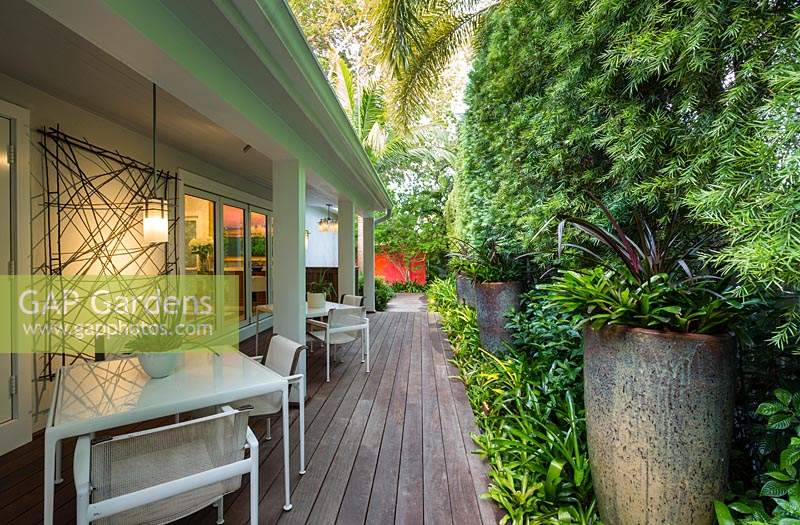 View down wooden decking with seating area in tropical garden. Von Phister Residence, Key West, Florida, USA. Garden design by Craig Reynolds.