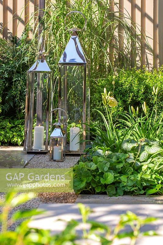 Group of tall metal lanterns with lit candles on the ground in 'The Landform Garden'