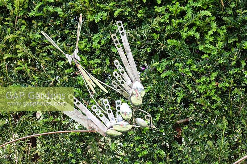 Birds and Bees - artwork made from steel cutlery - displayed against hedge