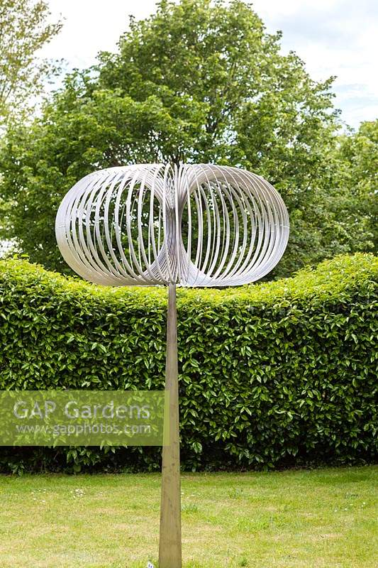 Torodial - sculpture in stainless steel -  on lawn with hedge and trees beyond