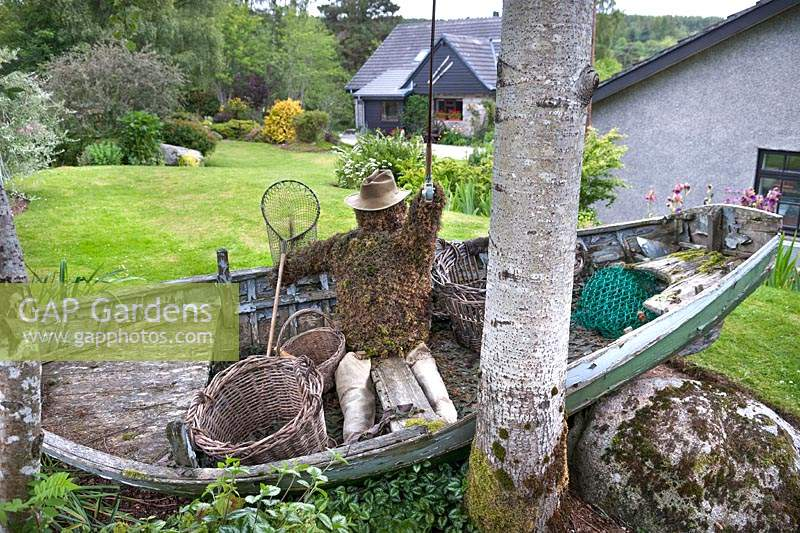 Garden feature of an old rowing boat, fly-fisherman made from moss and 