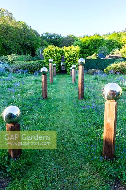 View up grass path with avenue of stainless steel mirror globes 