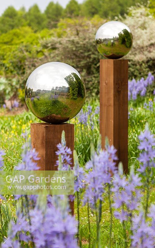 Close up of reflections in stainless steel mirror globes mounted on wooden posts