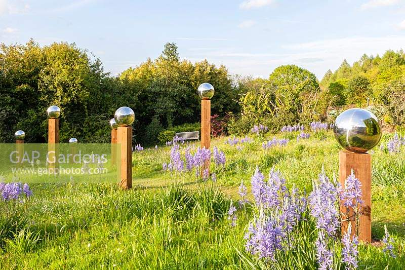Avenue of stainless steel mirror globes mounted on wooden posts in a meadow with 