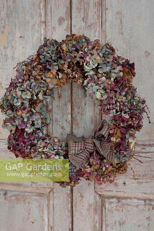 Multicoloured dried Hydrangea wreath on vintage French doors