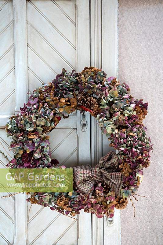 Multicoloured dried Hydrangea wreath on French cupboard door