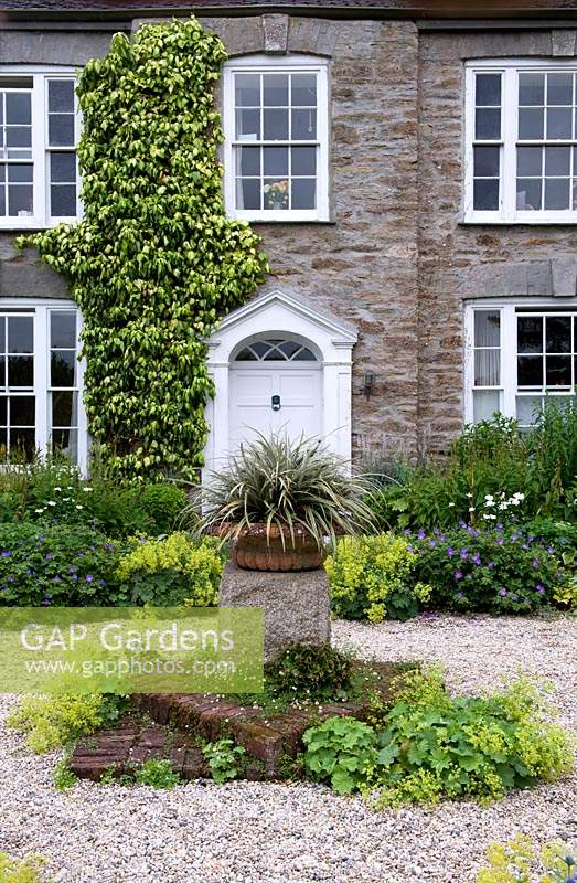 Graveled area with central stone plinth and potted plant, with view to front door surrounded by perennial borders. Bosvigo House, Cornwall, UK.