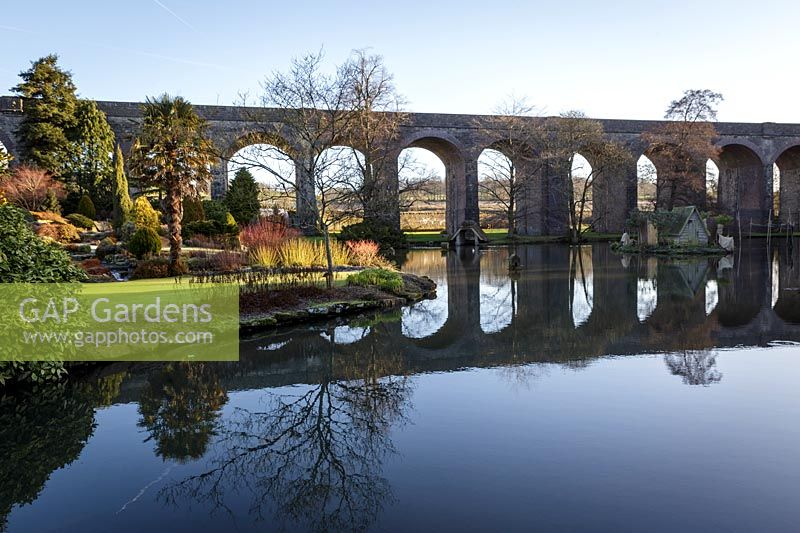 View across lake to viaduct. Kilver Court, Somerset, UK. Designed by Roger Saul of Mulberry.