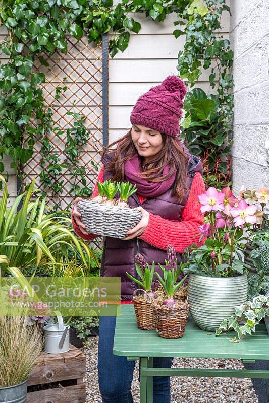 Woman holding basket with Hyacinthus in early-spring courtyard setting.