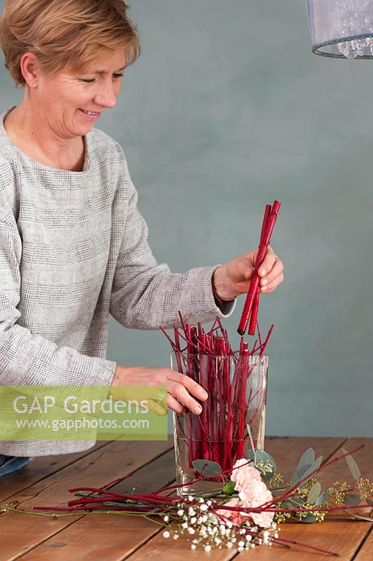 Woman arranging stems of Cornus - Dogwood in vase to create modern floral arrangement.