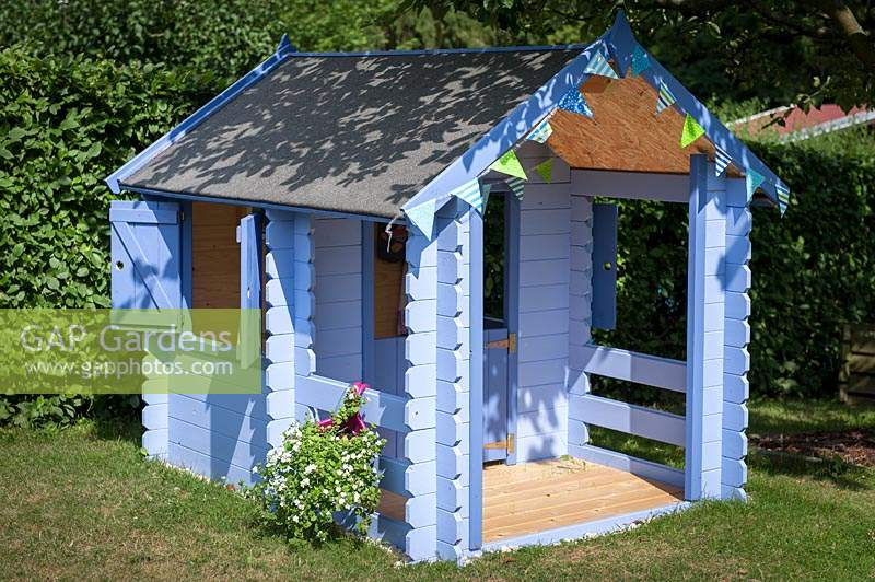 Blue painted children's playhouse in garden.