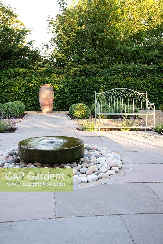 Formal garden with seating, circular millstone water feature and topiary
