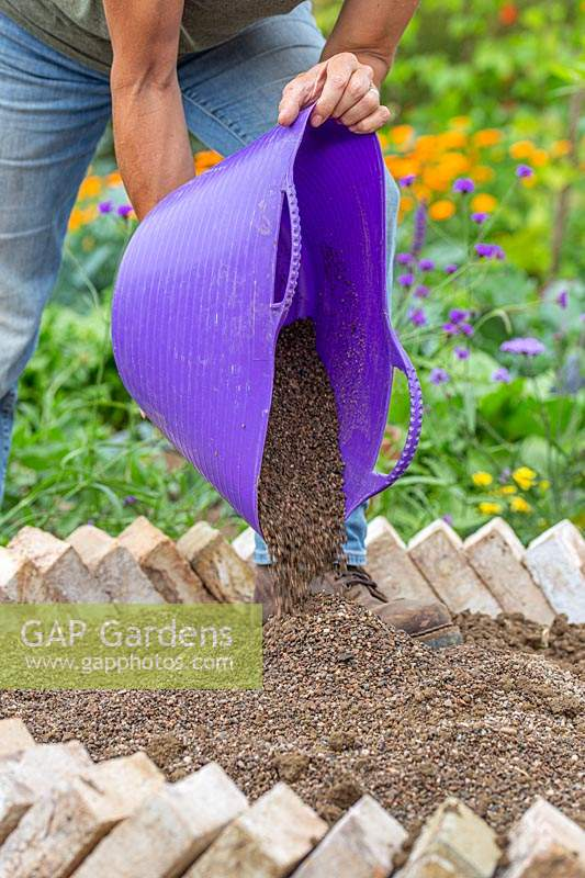 Woman adding well draining soil to raised bed