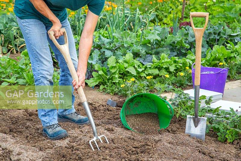 Woman forking in grit in preparation for herb garden