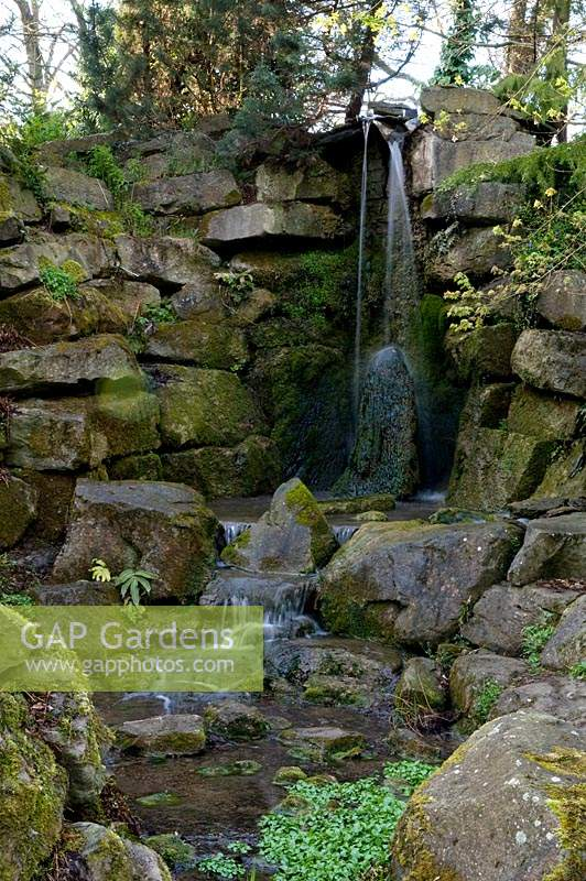 Waterfalls spill over rockery, at Abbey House Gardens, Malmesbury, UK.