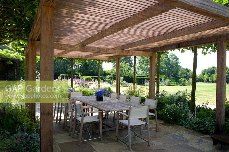 Wooden pergola shading dining area with table and chairs.