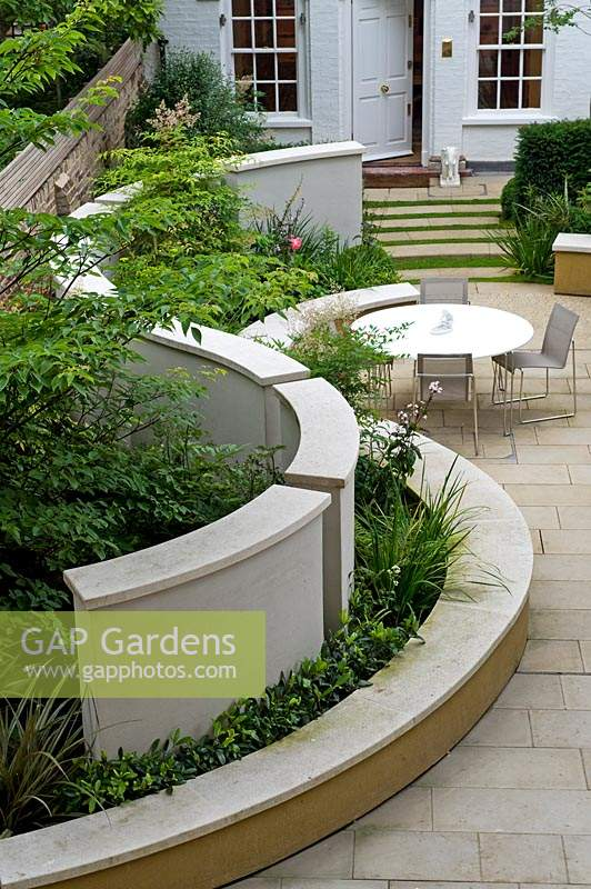 Greenery growing between curved wall and benching in modern urban garden.