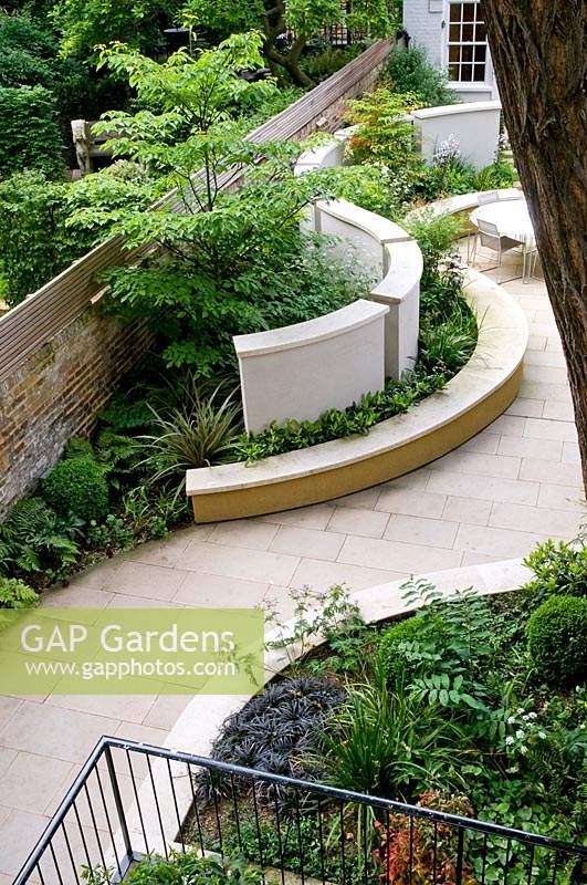 View down into paved urban garden, with curved borders of mixed planting.