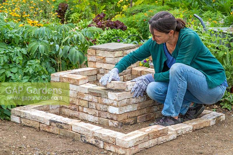 Woman adding bricks to create two L-shaped tiered beds around the corner pedestal.