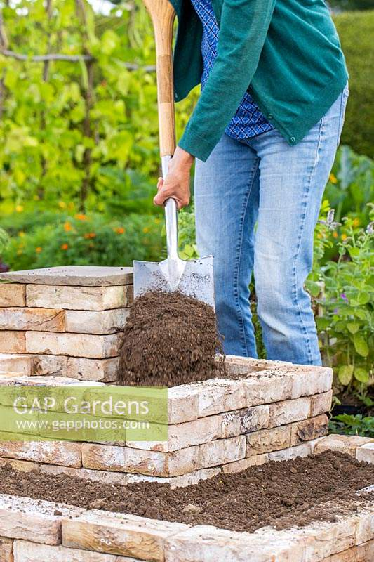 Woman adding well-draining soil to tiered brick garden using a spade.