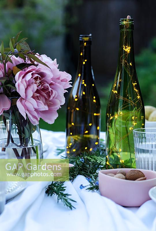 Fairylights in bottles create centrepieces on dining table in garden.