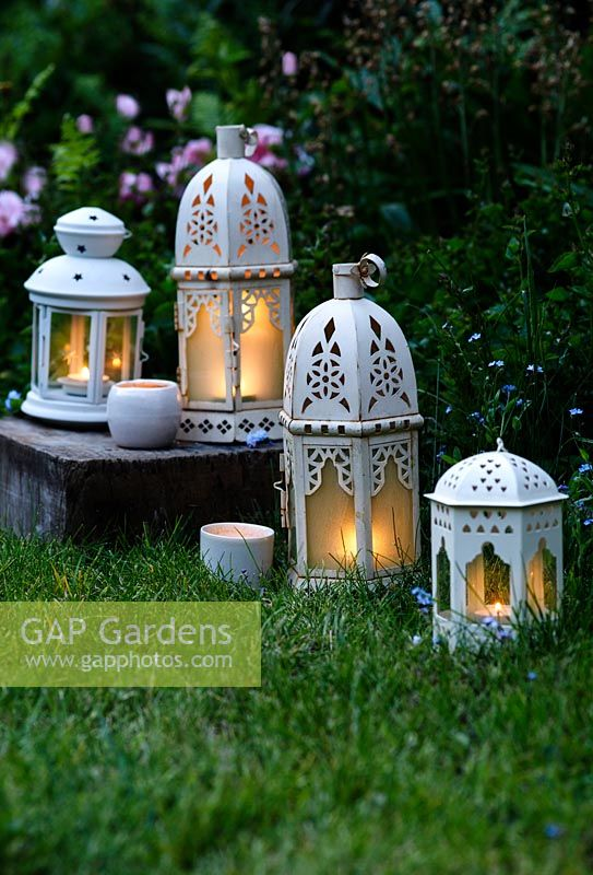 An eclectic mix of white candle lanterns in garden at dusk.